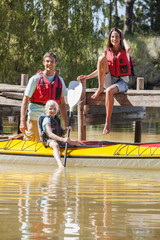 Family on dock and in kayak on lake