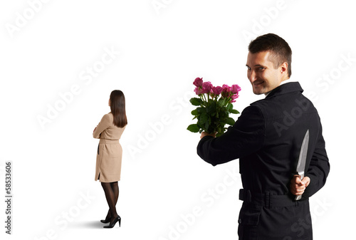 man with knife standing behind woman
