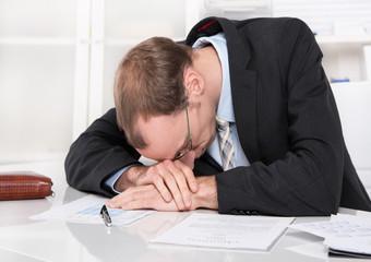 Mann frustriert im Büro - Burnout oder Müdigkeit