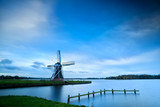 Dutch windmill by lake with long exposure