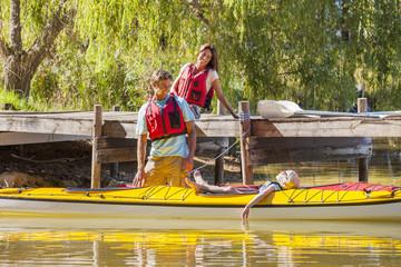 Parents watching daughter in kayak on lake