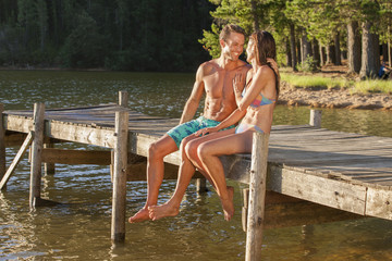 Happy couple hugging at the edge of dock over lake
