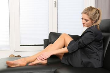hübsche Frau massiert sich die Füße