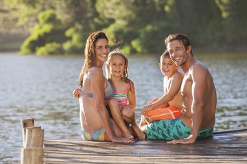 Happy family sitting at the edge of dock over lake