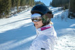 Woman in goggles and helmet stay on the snow