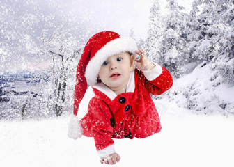 Baby in christmas hat outdoors with snow