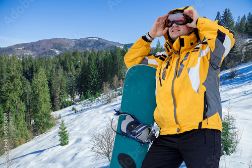 Men in goggles stay with snowboard on the top of mountain