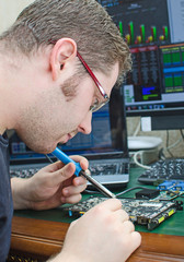Worker repairing computer equipment with soldering iron