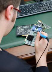 Worker repairing computer equipment with soldering iron