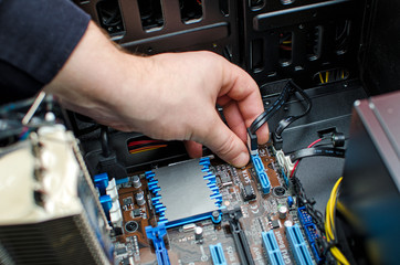 Hands of technician installing HDD on motherboard
