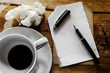Cup of coffee with notepad, pen and crumpled paper on wooden bac