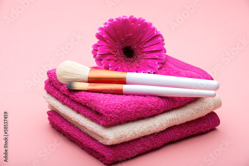 Brushes for make-up  on towel with  big pink flower