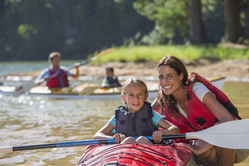 Portrait of smiling mother and daughter in kayak on lake