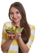 Junge Frau mit sehr langen Haaren und Salat in der Hand