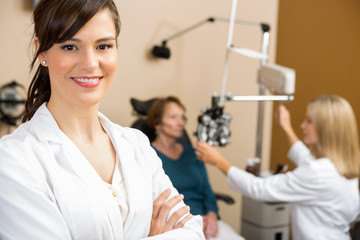 Female Optometrist With Colleague Examining Patient