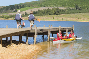 Family on dock and in kayaks on lake