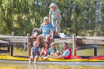 Smiling multi-generation family on dock and in kayak on lake