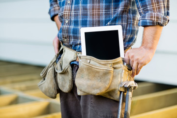 Construction Worker With Tablet Computer In Toolbelt