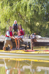 Portrait of smiling family at dock on lake with kayak