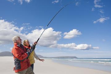 Happy senior couple fishing on sunny beach
