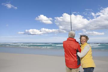 Senior couple with fishing rod on sunny beach