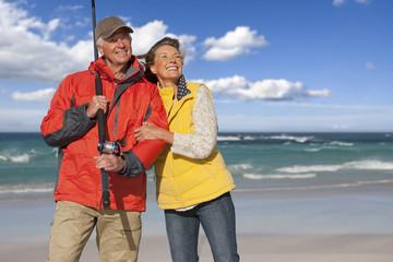 Happy senior couple with fishing rod on sunny beach