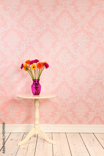 Vintage wall and wooden floor with vase flowers on table