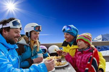 Ski - skiers enjoying lunch in winter mountains