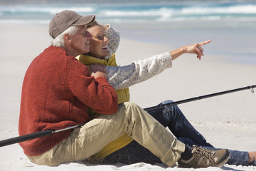 Happy senior couple with fishing rod sitting on sunny beach