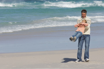 Happy father lifting daughter on sunny beach