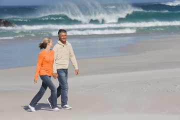 Couple walking on sunny beach
