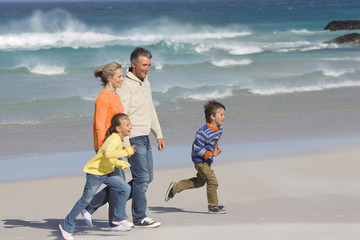 Happy family walking on sunny beach