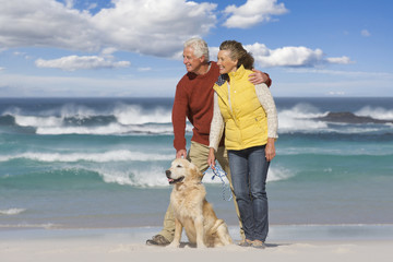 Senior couple with dog on sunny beach