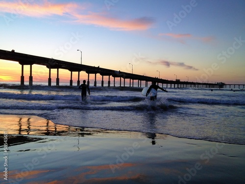 Surfers at Sunset at Ocean Beach Pier San Diego California USA