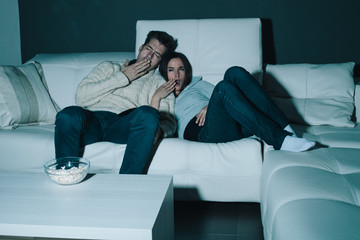 Couple watching TV late at night yawning and falling asleep