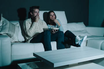 Couple enjoying watching a movie at home laughing on the couch
