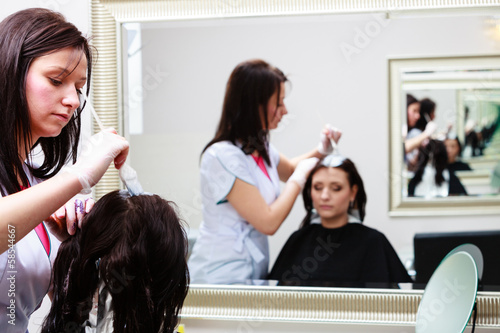 hairdresser applying color female customer at salon