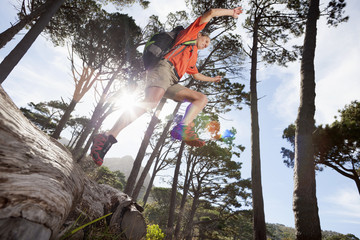 Woman with backpack jumping over log in woods