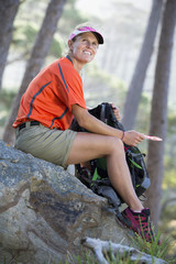 Smiling woman with backpack and compass in woods