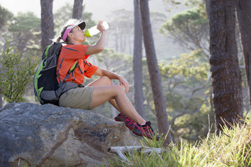 Woman with backpack drinking water in woods