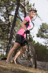 Portrait of smiling woman with mountain bike in woods