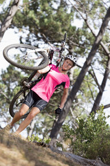 Woman carrying mountain bike in woods