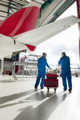 Engineers with tool box under passenger jet in hangar