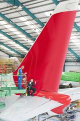 Engineers inspecting tail of passenger jet in hangar