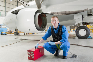 Engineer with tool box near passenger jet in hangar