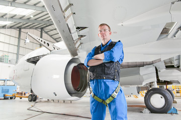 Engineer under wing of passenger jet in hangar