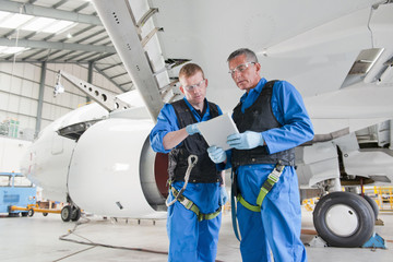 Engineers reviewing paperwork under passenger jet in hangar