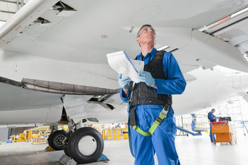 Engineer with paperwork below passenger jet in hangar