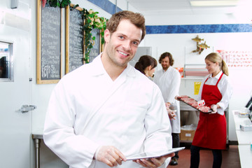 Employee checking inventory in butcher shop with tablet