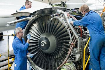 Engineers assembling engine of passenger jet in hangar